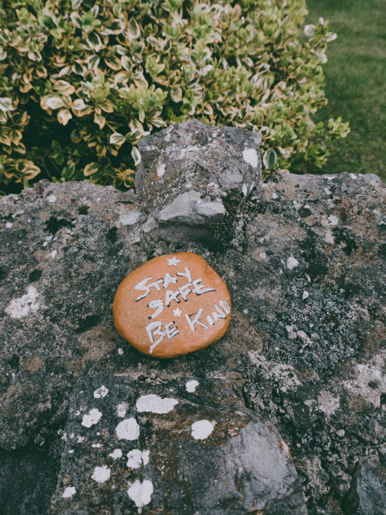A rock with text that says be safe be kind on it